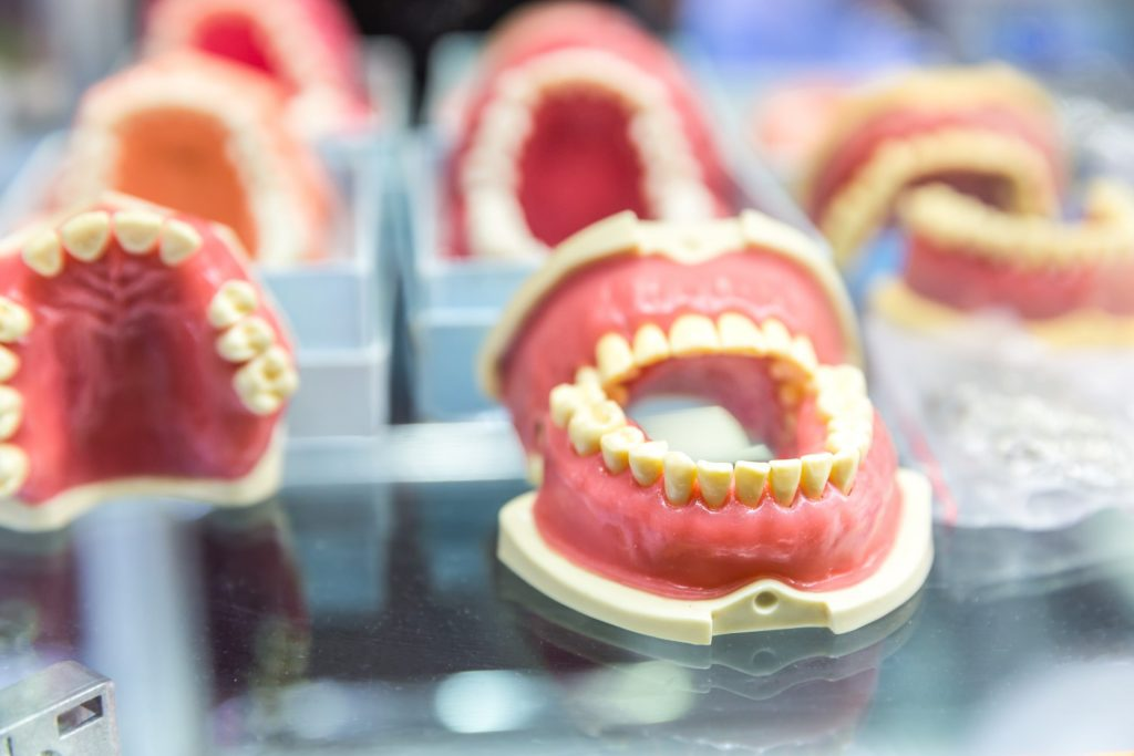 Image of multiple rows of full dentures on metal table