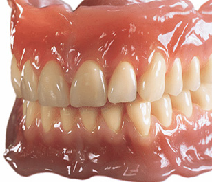 Image of glossy looking dentures on white background