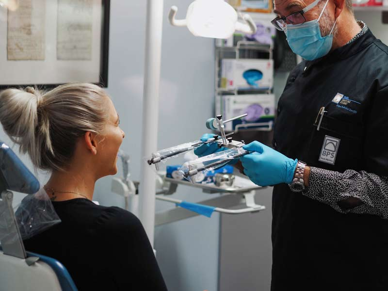 Image of dentist with metal contraption standing in front of blonde patient   Featured image for dentures keep falling out blog.